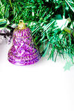 Purple bell on green. Purple bell decoration and Christmas ornament on a green and white background royalty free stock photo