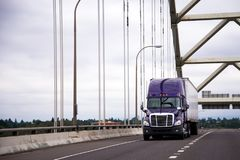 Purple big rig semi truck with dry van trailer for long haul car. Modern purple reliable American big rig semi truck with dry van semi trailer for long haul Stock Image