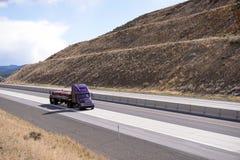 Purple big rig semi truck with flat bed semi trailer transportin Stock Photos