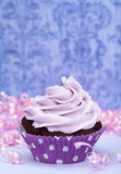 Purple Birthday Cupcake. A chocolate birthday cupcake with purple icing and pink ribbons. Copy space royalty free stock photography