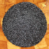 Purple Black Rice Round Square. Organic purple black rice shaped into a circle in a wood bowl, square photo Royalty Free Stock Photos