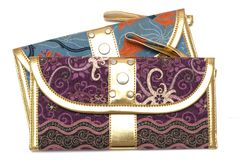 A purple and blue pouch with zipper puller. A front facing photo taken on a blue and a purple gold rimmed pouch with zipper puller hand strap against a white Royalty Free Stock Images