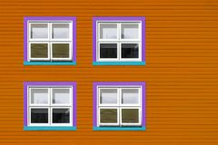 Purple and blue windows on orange wall. Purple, blue and white windows on a orange wooden wall. Minimalism style of the houses of Iles de la Magdalen, Canada, in stock photo