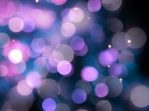 Purple blurred round shiny blurred lights abstract with bright sparkles on a black background royalty free stock images