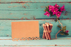 Purple bougainvillea flowers, colorful wooden pencils next to vintage empty card over wooden table stock images