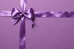 Purple bow and ribbon isolated on purple background stock photography