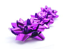 Purple Bow Ribbons. Puple Bow against a white background.  The light shines from thess bows to brings to thought the brightness of every gift we give and receive Royalty Free Stock Photo