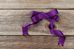 Purple bow on wooden background Stock Images