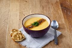 Ceramic bowl of pumpkin soup on napkin over rustic wooden background, close-up, selective focus, top view. stock photos