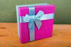purple box for Christmas gifts on a green background, Christmas gifts, blue ribbon, blue bow stock image