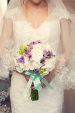 Purple bridal bouquet in the hands of. Purple bridal bouquet with green ribbon in the hands Royalty Free Stock Images