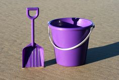 Purple bucket and spade. A purple bucket and spade on the beach royalty free stock images