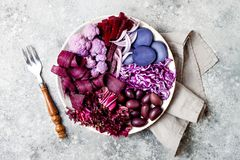 Purple Buddha bowl with spiral carrots, cauliflower, beet, onion, potato, shredded red cabbage, radicchio salad, kalamata olives. Vegan detox veggie bowl Stock Photos