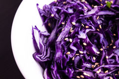 Purple cabbage slaw with sesame seeds. In a white bowl dark background, close up stock photo