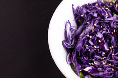Purple cabbage slaw with sesame seeds. In a white bowl dark background, close up stock photography