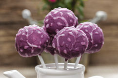 Purple cake pops in white ceramic pot on wooden background. Royalty Free Stock Photos