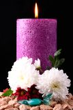 The purple candel. A pink and purple candle surronding with flowers and brown decoration stones, a glas item in the mittle Stock Image