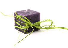 Purple candle with green rafia Stock Photos