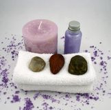 Purple Candle and Massage Oil. A purple candle, massage oil, facecloths, stones and bath crystals Stock Photography