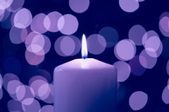 Purple Candlelight. Burning candle with bokeh Christmas light background colorized in purple Royalty Free Stock Image