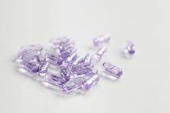 Purple Capsule pills. Use in pharmaceutical manufacturing, drug, medicine, garlic oil, fish liver oil Stock Photos