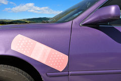 Purple car with a bandaid on side dent. A dented car with a large band aid on the side Stock Photography