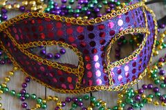 Sequined Mardi Gras mask with beads. Purple carnival mask with colorful strands of beads stock photos