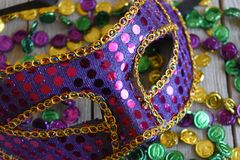 Sequined Mardi Gras mask with beads. Purple carnival mask with colorful strands of beads royalty free stock images
