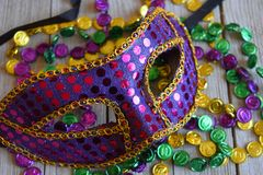 Sequined Mardi Gras mask with beads. Purple carnival mask with colorful strands of beads stock image