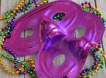 Mardi Gras mask with beads on a wood background. Purple carnival mask with a string of colorful beads royalty free stock photo