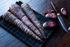 Purple Carrots on Dark Wooden Surface. royalty free stock photos
