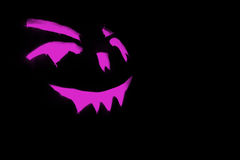 Purple carved face of pumpkin glowing on Halloween black background Stock Photos