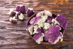 Purple cauliflower on a wooden table Stock Photos