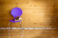 Purple chair with opened book next wooden wall Royalty Free Stock Image