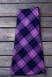 Purple checkered skirt. Grey wooden surface background Royalty Free Stock Photography