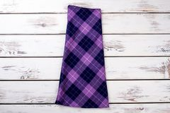 Purple checkered skirt. Wooden desks surface background Royalty Free Stock Images
