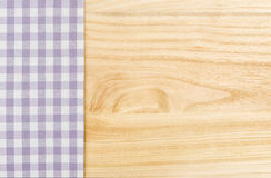 Purple checkered table cloth on a wooden background. Violet checkered table cloth on a wooden background Royalty Free Stock Images