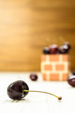 A Purple Cherry. A Purple Cherry in front of cherry group on the wood table and brown wood background Royalty Free Stock Image