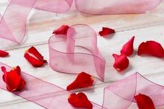 Purple Chiffon Ribbon Heart, Streamers, and Rose Petals Stock Photos