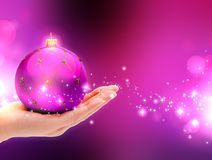 Purple Christmas ball on female hands. Stock Image