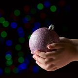 Purple christmas ball in the kid's hands on the black background. With colorful bokeh Royalty Free Stock Photo