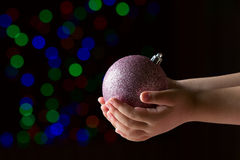Purple christmas ball in the kid's hands on the black background. With colorful bokeh Royalty Free Stock Photography