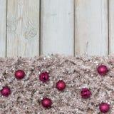 Purple christmas balls on silver tree garland Royalty Free Stock Photos