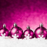 Purple christmas balls on snow Royalty Free Stock Photos