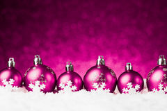 Purple christmas balls on snow Stock Images