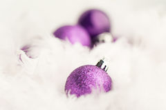 Purple Christmas Baubles. In white feather Stock Photography