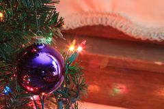 A Purple Christmas bulb shot closeup. On a Christmas tree with Christmas lights by a window and a curtain Royalty Free Stock Photography