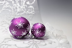 Purple Christmas decorations with silver ornament. Purple Christmas baubles with silver ornament on silver background, text space. Shallow DOF, focus on the knot stock photography