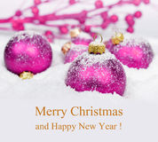 Purple Christmas decorations in snow. Royalty Free Stock Images