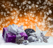 Purple Christmas package , gift of a silver ribbon. Jingle bells , silver christmas balls and christmas stars put on snow. Abstrac. T multicolored blurred Stock Photography